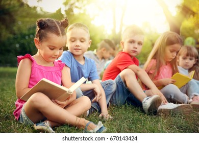 Cute children reading books in park. School holidays concept