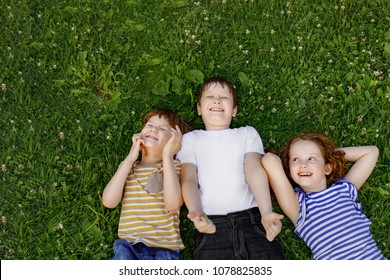 Cute children resting on the grass in summer outdoor. Family, happy childhood concept.