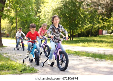 Cute children riding bicycles in park on sunny day