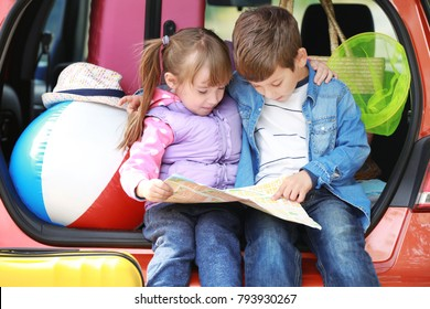 Cute children with road map near modern car prepared for traveling