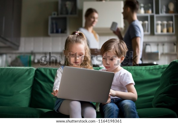 Cute children sister and brother watching online cartoons on laptop while parents talking in the kitchen, curious siblings boy girl using pc at home, kids computer addiction parental control concept