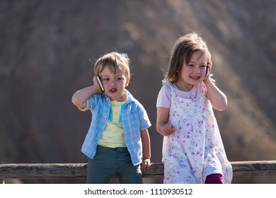 Cute children sitting on road railing and calling with smartphone
