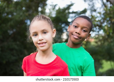 Cute children smiling at camera outside in the park