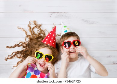 Cute children with sunglasses, hold candles 2018, lying on the wooden floor. High top view.