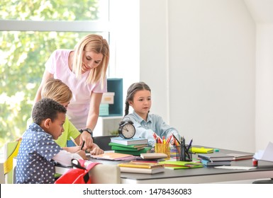 Cute children with teacher during lesson in classroom
