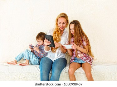 Cute children and their beautiful young mother sit together, using a digital tablet and smiling, on background a light wall of fur