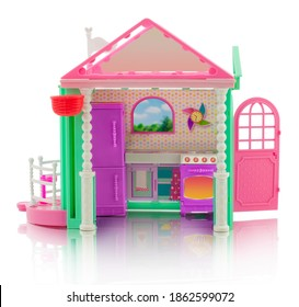 cute children's little house - a toy. Plastic dollhouse. Small house with kitchen, stove, oven, terrace, door, clock and refrigerator. Isolated on white background with shadow reflection.