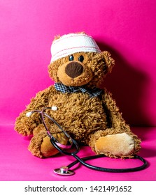 cute child's teddy bear with a head bandage and stethoscope for concept of domestic mishap and hospital treatment over nursing pink background