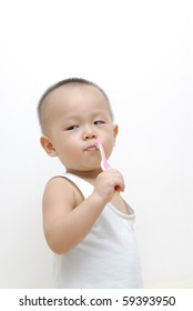 it is a cute chinese baby, he is brushing his teeth. isolated