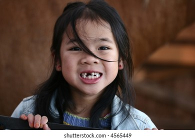 cute  chinese child portrait smiling with some missing tooth