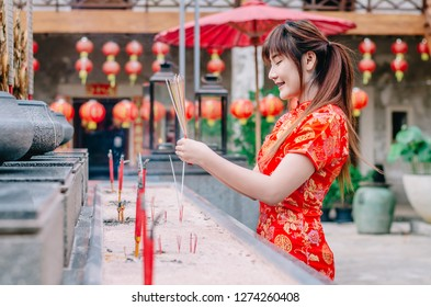 Cute chinese girl dressing traditional red Cheongsam suit burning incense sticks and pay respect and praying to Chinese God for lucky