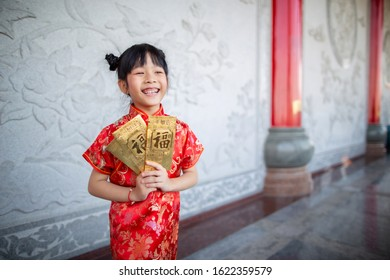 Cute Chinese girl showing her gold gift envelopes that her receive on Chinese New Year celebration with background of the beautiful Chinese temple.  The words on envelopes mean rich and prosperous.