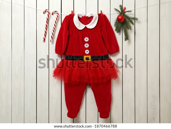 Cute Christmas baby clothes, fir branches and candy canes hanging on white wooden wall