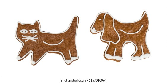 Cute Christmas gingerbreads in cat and dog shape. Two sweet fragrant candies decorated by icing. Traditional homemade confections. Idea of Xmas, Children's day, party. Isolated on white background.