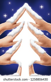 Cute Christmas themed concept of a Christmas tree shape made by children hands covered with snow on blue starry sky background and white copyspace in the center, artistic photo illustration