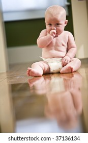 Cute chubby seven month old baby wearing diaper sitting on floor