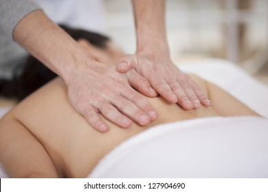 Cute chubby woman getting a back massage at a spa