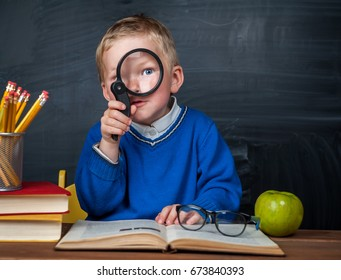Cute clever boy is sitting at a desk with magnifying glass in hand. Child is reading a book with a blackboard on a background. Ready for school. Back to school. Apple and books on desk.