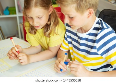 Cute clever schoolchildren are came back to school and studying together at the table in classroom