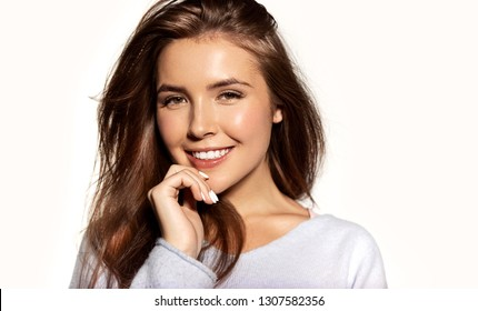 Cute close-up portrait of girl with beautiful white smile. Charming young female in warm blue pullover standing indoors on light background. Happiness and beauty concept