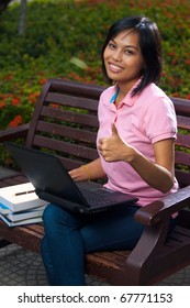 A cute college student wearing pink shirt using a black laptop on lap on outdoor bench gives a thumb up with a smile.  20s female Asian Thai model of Chinese descent looking at camera