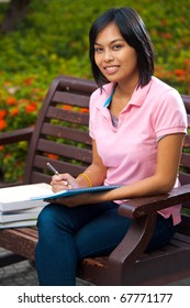 A cute college student wearing pink shirt smiling while studying outside on university campus bench surrounded by flowers.  20s female Asian Thai model of Chinese descent looking at camera