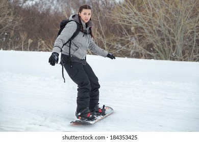 A cute concerned facial expression of a brunette beginner female snowboarder while is learning, for her first time, to ski with snowboard; during a cloudy day on a easy slope.