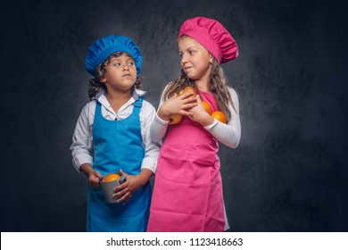 Cute cook couple. Little boy with brown curly hair dressed in a blue cook uniform and beautiful schoolgirl dressed in a pink cook uniform, poses with cookware and fruits at a studio. Isolated on the
