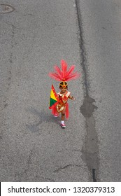 Cute costumed child on the Junior Caribana Parade route with oreo cookie and flag in Toronto, Ontario, Canada - July 19, 2008