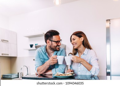 Cute couple cheering with cup of coffee or tea.
