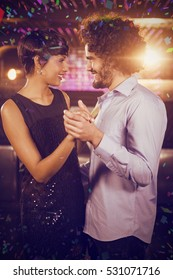 Cute couple dancing together on dance floor against flying colours