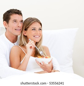 Cute couple eating breakfast together in the bedroom