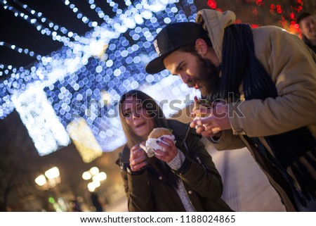 cute couple eating burger under a christmas lights