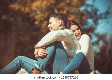 Cute couple enjoying their love outdoors, sitting on the grass in the park on a sunny day