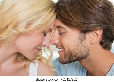 Cute couple facing each other with eyes closed at home in the living room