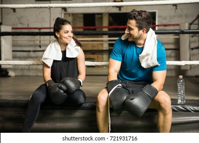 Cute couple flirting and talking while taking a break from training in a boxing gym