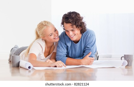 Cute couple getting ready to move in a new house while lying on the floor