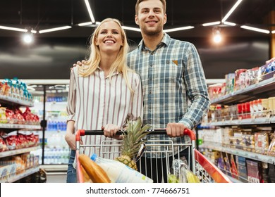 Cute couple grocery shopping together at the supermarket