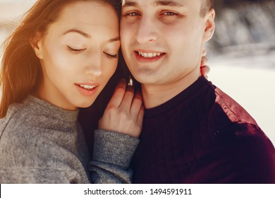 Cute couple have fun. Boy and girl in a winter park. Man in a red sweater. Brunette in a gray sweater