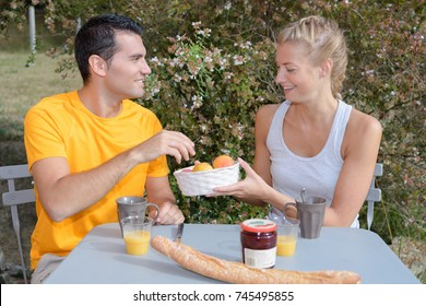 cute couple having breakfast together outdoors
