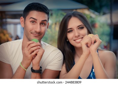 Cute Couple Having Macarons at a Restaurant - Funny young couple eating French macaron dessert