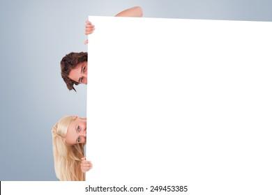 Cute Couple hiding behind a whiteboard against grey vignette