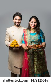 Cute couple holding thali having diya and sweet laddu food