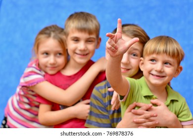 Cute couple of kids in casual clothes are giving high five, looking at camera and smiling, on gray background