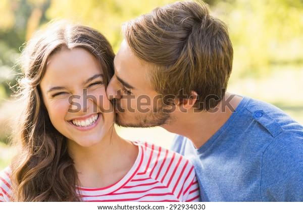 陽気な日に公園でキスをするかわいい夫婦