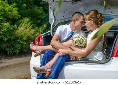 Cute couple looking at each other while seated together in trunk of white car with open lid near cornfield