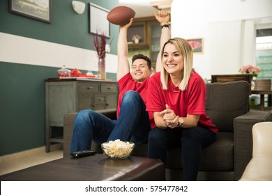 Cute couple looking excited and happy after their favorite football team scored a touchdown