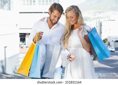 Cute couple looking at their shopping purchases on a sunny day in the city