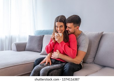 Cute couple in love in the weekend morning. They are hugging on the sofa indoors at home, wearing casual outfits. There are some sweet treats at the table near them, interior is modern and cozy
