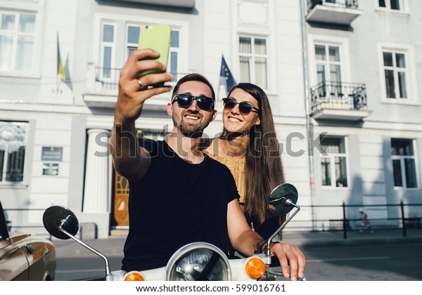 Cute couple make selfie on a scooter at sunny day in the city